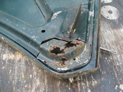 rust damage at hood hinge corner